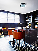Leather chairs and antique leather desk in the study with dark wall shelf and leather wall covering