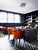 Lederstühle und antiker Lederschreibtisch im Arbeitszimmer mit dunklem Wandregal und Leder-Wandverkleidung