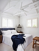 Double bed and ceiling fan in the bedroom with white wooden roof structure