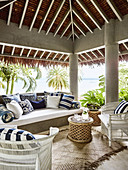 Outdoor furniture with blue and white patterned cushions on a covered terrace with sea views