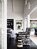 Open living space in black and white, designer armchairs and sofa in front of the terrace opening