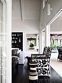 Offener Wohnraum in Schwarz und Weiß, Designer-Armlehnsessel und Sofa vor Terrassenöffnung