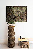 Plant bowl on wooden sculpture, picture in white corridor above
