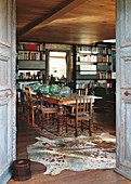 View through open wooden doors into dining room with long table, chairs and bookcases