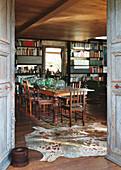 Blick durch geöffnete Holztüren in den Speisesaal mit langem Tisch, Stühlen und Bücherregalen