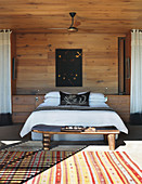 Double bed in sunny wood-panelled bedroom
