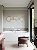 Designer bathtub and pouffe in bathroom with access to terrace