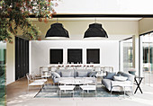 White and pale grey furniture in lounge area with long dining table in background