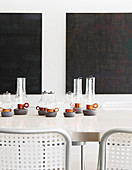 Candle lanterns on long dining table in front of black artworks on wall