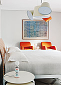Double bed, side table and two orange armchairs in bright bedroom