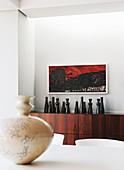 Black vases on exotic-wood sideboard below artwork on wall