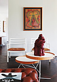 Sculpture on side table, two chairs and artwork on wall