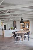 weiße Küche mit Kücheninsel und Holztisch mit Stühlen in offenem Wohnraum in umgebautem Stall
