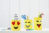 Hand-made emoji desk organisers made from tin cans
