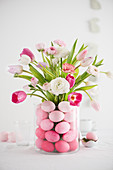Easter bouquet in glass vase full of Easter eggs