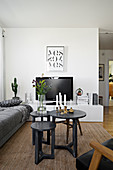 Set of three tables, grey sofa and TV on low, white sideboard in living room