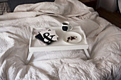 Black and white utensils on a breakfast tray on a bed