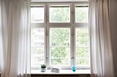 Fenster mit hellem Vorhang
