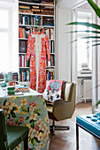 Retro armchair at table with floral tablecloth in front of bookcase