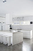 Island counter and concrete worksurfaces in white kitchen