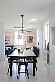 Schwarzer Esstisch mit Windsorstühlen vor dem Wohnzimmer