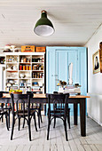 Dining table and chairs in kitchen with blue lacquered closet and vintage shelf