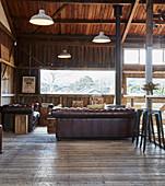 Vintage Ledergarnitur und Barhocker in offenem Wohnraum mit Holzverkleidung