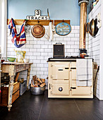 Old wood stove and vintage table in kitchen with white tiled wall