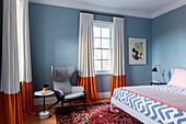 Gray wing chair, side table and double bed in gray-blue bedroom