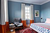 Grauer Ohrensessel, Beistelltisch und Doppelbett in graublauem Schlafzimmer