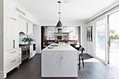 Küchenzeile und Marmor-Kücheninsel vor Terrassentür in offenem Wohnraum