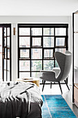 Double bed, side table and wing chair in the bedroom with industrial window