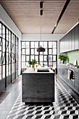 Black kitchen unit with green wall tiles and kitchen island in open kitchen with industrial window