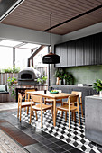 Black kitchenette with green wall tiles and dining area, pizza oven on the terrace in the background