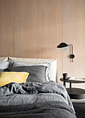 Double bed and wall lamp on room divider with wooden paneling