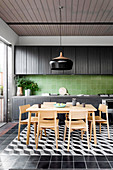 Dining area in front of a black kitchenette with green wall tiles