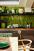 View across dining table to kitchen counter with green tiled splashback