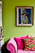 Painting of woman on green wall above hot-pink sofa