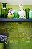Bird ornament and green vases on shelf on green wall