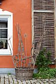 Skulptural geflochtener Weidenkorb als Deko vor dem Haus