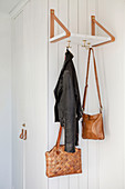 Shelf hung from two leather loops with hooks used as coat pegs
