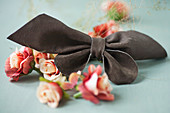 Leather bow and fabric flowers on grey surface