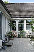 Gepflasterter Hof vor einem Haus mit Sprossenfenstern