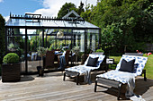 Two loungers on sunny wooden deck outside conservatory