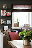 View of sofa with scatter cushions, window and bookcase on dark wall across coffee table