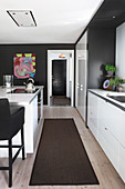 Island counter in black and white fitted kitchen