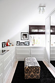White fitted drawers and ottoman in dressing room