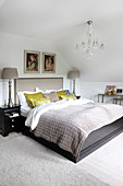 Double bed below chandelier in attic bedroom