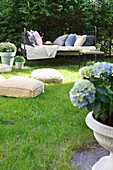 Floor cushions on lawn and metal bed used as couch in summery garden