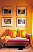 Four pictures on yellow wall above antique couch with striped scatter cushions